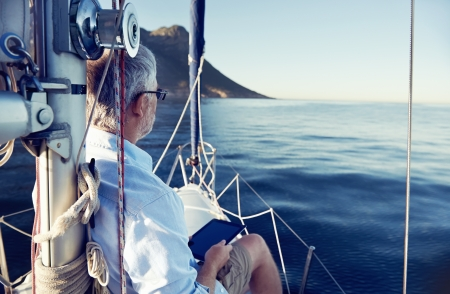sailing yacht: sailing man reading tablet computer on boat with modern technology and carefree retired senior successful lifestyle Stock Photo