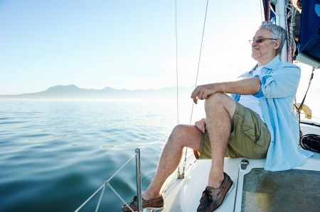boat deck: relaxing man sitting on boat sailing on ocean happy and carefree Stock Photo