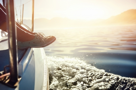 sail boat: feet on boat sailing at sunrise lifestyle Stock Photo