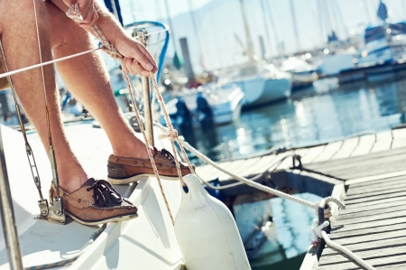 mooring: portrait of senior man tying knot and securing a mooring for his hobby yacht sail boat