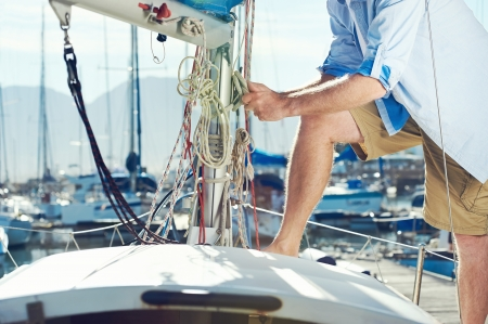 securing: portrait of senior man tying knot and securing a mooring for his hobby yacht sail boat