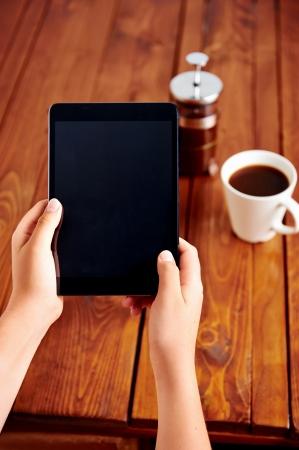 Jonge vrouw maakt gebruik van tablet, terwijl ontspannen thuis met een kopje koffie op de bank bank