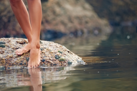 Woman on roack at beach dipping toes in water, having fun outdoor lifestyle