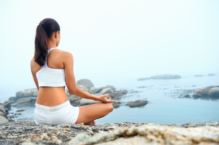 meditate: yoga beach woman doing pose at the ocean for zen health and peaceful lifestyle Stock Photo