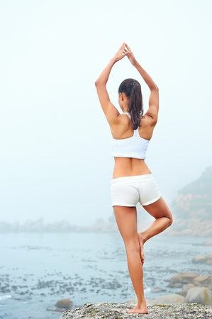 yoga beach woman doing pose at the ocean for zen health and peaceful lifestyle photo