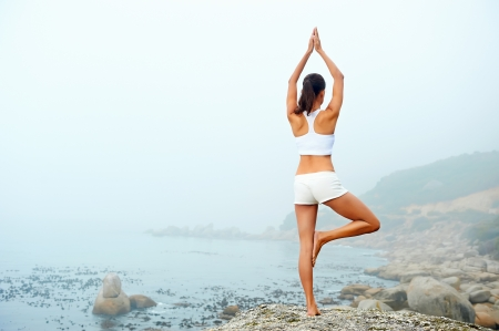 wellness: yoga beach woman doing pose at the ocean for zen health and peaceful lifestyle Stock Photo