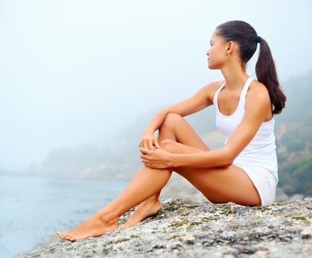 a serene life: yoga beach woman doing pose at the ocean for zen health and peaceful lifestyle Stock Photo