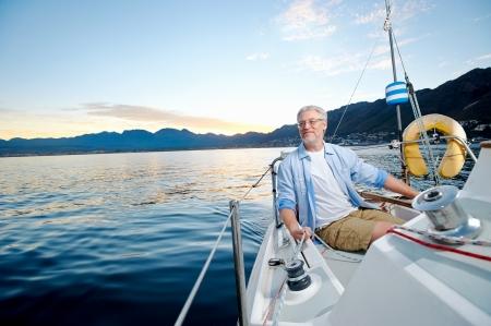 jubilados: despreocupado feliz vela hombre retrato de hombre jubilado maduro en el barco al mar al amanecer Foto de archivo