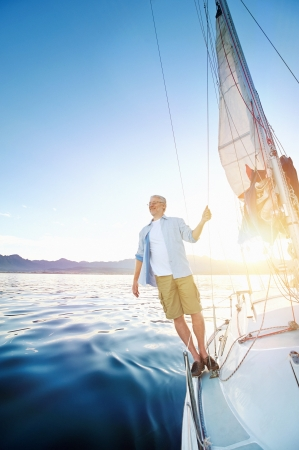 sail boat: sunrise sailing man on boat in ocean with flare and sunlight on calm morning on the water Stock Photo