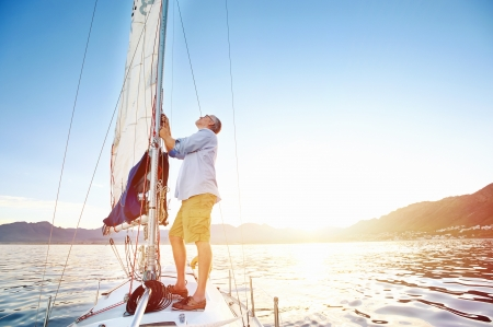 sailing boat: sunrise sailing man on boat in ocean with flare and sunlight on calm morning on the water Stock Photo