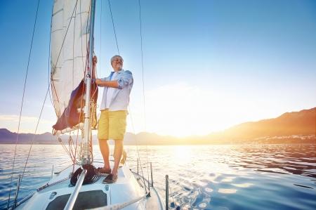 voile bateau: Lever l'homme de la voile sur le bateau dans l'oc�an avec la fus�e et la lumi�re du soleil sur une mer calme matin sur l'eau Banque d'images