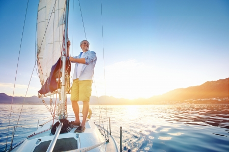 alone man: sunrise sailing man on boat in ocean with flare and sunlight on calm morning on the water Stock Photo