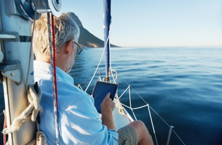 sailing: sailing man reading tablet computer on boat with modern technology and carefree retired senior successful lifestyle Stock Photo