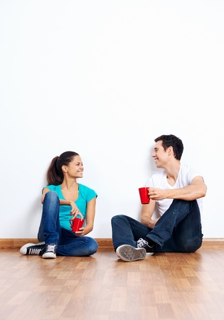 couple moving into empty new home sitting on floor together and drinking coffee Stock Photo - 20571220