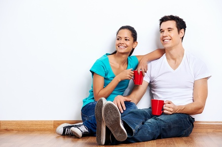 couple moving into empty new home sitting on floor together and drinking coffee Stock Photo - 20571288