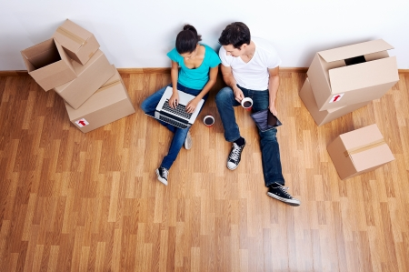 moving box: overhead view of couple sitting on floor together using computer wireless internet while moving into new home Stock Photo