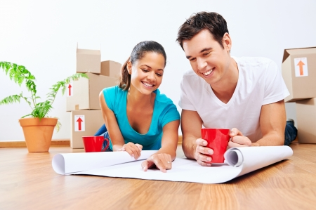 couple lying on floor looking at plans of new house together while drinking coffee and laughing