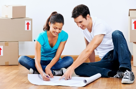 couple moving into new home looking at floor plans together photo