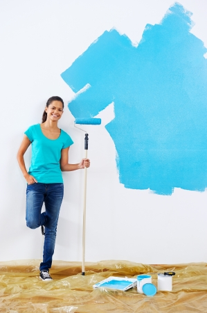 paintrush: portrait of woman posing with paint roller in new apartment renovation Stock Photo