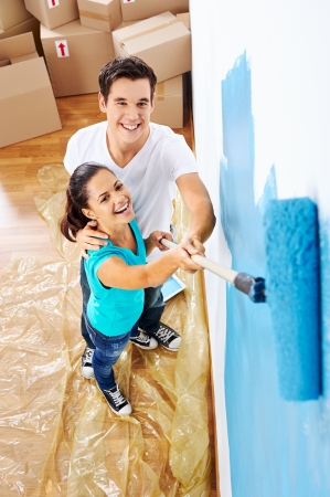 overhead view of couple having fun renovating their new home together with blue paint on a roller Stock Photo - 20571321