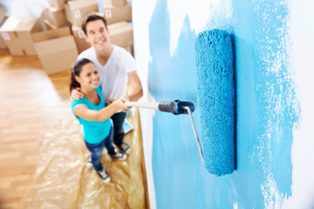 house renovation: overhead view of couple having fun renovating their new home together with blue paint on a roller