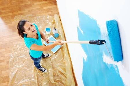 liggande: ovanifrån av kvinnan painging nya lägenhet stående på trägolv