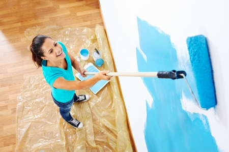 paintrush: overhead view of woman painging new apartment standing on wooden floor