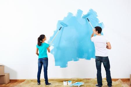 Coppia pittura la nuova casa insieme con il colore blu relazione felice e spensierata Archivio Fotografico - 20571238
