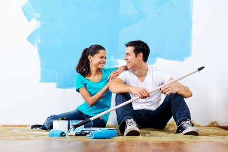 couple painting new home together with blue color happy and carefree relationship photo
