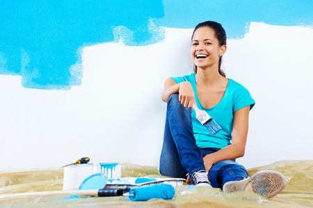 confident young woman portrait while painting new apartment renovating with blue color paint photo