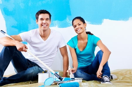 cute couple painting new home together portrait while sitting on wooden floor Stock Photo - 20571340
