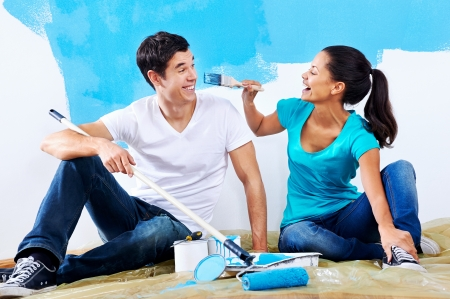 paintrush: cute couple painting new home together portrait while sitting on wooden floor