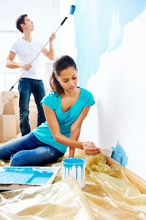 house renovation: couple painting new home together with blue color happy and carefree relationship