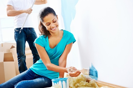 couple painting new home together with blue color happy and carefree relationship Stock Photo - 20571301