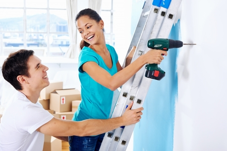 couple drilling in wall doing diy at new home after moving in together photo