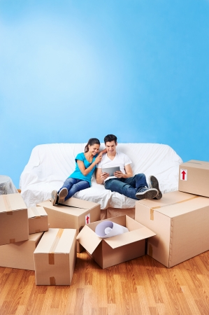 first move: couple moving in together relaxing on sofa couch with laptop tablet computer and boxes