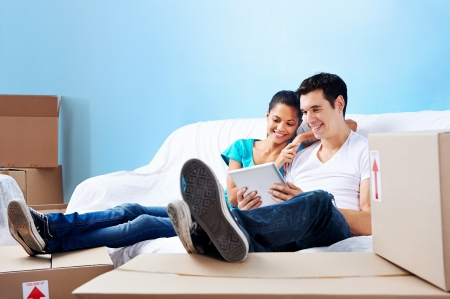couple moving in together relaxing on sofa couch with laptop tablet computer and boxes Stock Photo - 20571308