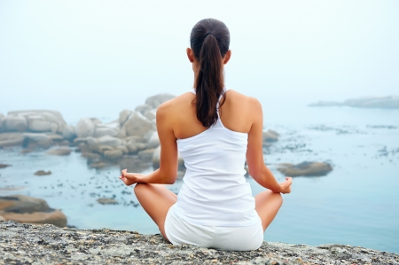 meditating: yoga beach woman doing pose at the ocean for zen health and peaceful lifestyle Stock Photo
