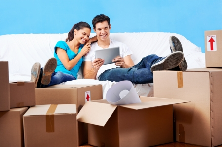 packing boxes: couple moving in together relaxing on sofa couch with laptop tablet computer and boxes