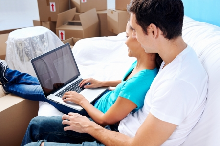 couple moving in together relaxing on sofa couch with laptop tablet computer and boxes Stock Photo - 20571312