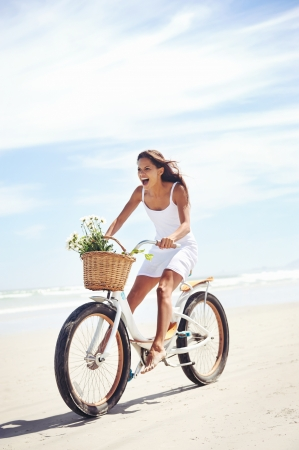 woman riding bicycle on beach in summer Stok Fotoğraf
