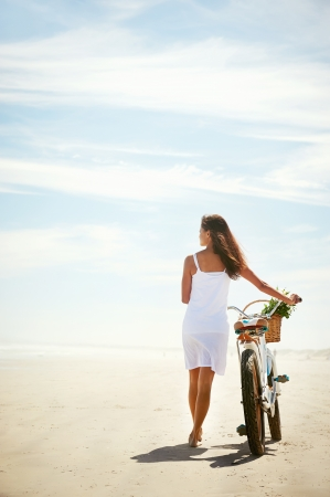 girl on bike: Woman walking with bicycle along beach sand summer lifestyle carefree