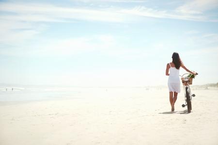 genießen: Frau zu Fuß mit dem Fahrrad entlang Strandsand Sommer Lebensstil sorglos Lizenzfreie Bilder