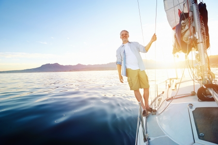 sunrise sailing man on boat in ocean with flare and sunlight on calm morning on the water photo