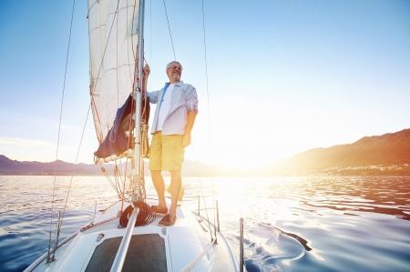 フレアと水の穏やかな朝の日光の海でボートに乗って日の出セーリング男 写真素材