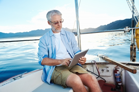 sailors: sailing man reading tablet computer on boat with modern technology and carefree retired senior successful lifestyle Stock Photo