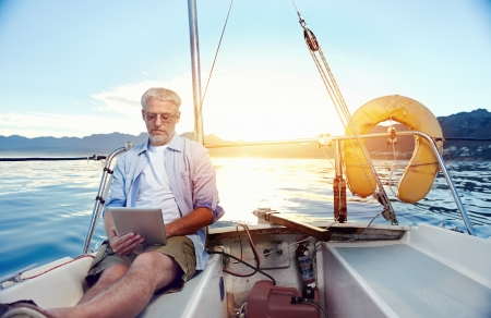 sailing man reading tablet computer on boat with modern technology and carefree retired senior successful lifestyle Stock Photo - 20863380