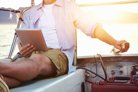sailboats: sailing man reading tablet computer on boat with modern technology and carefree retired senior successful lifestyle Stock Photo