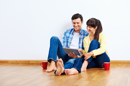 Couple moving in to new home and using wireless internet on tablet computer Stock Photo - 20863410
