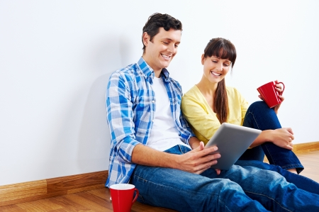 Couple moving in to new home and using wireless internet on tablet computer Stock Photo - 20863418
